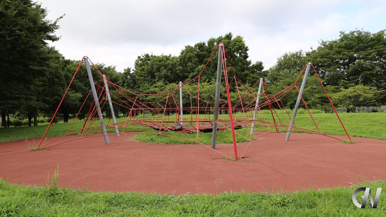 赤いロープのネットでクモの形を模した遊具